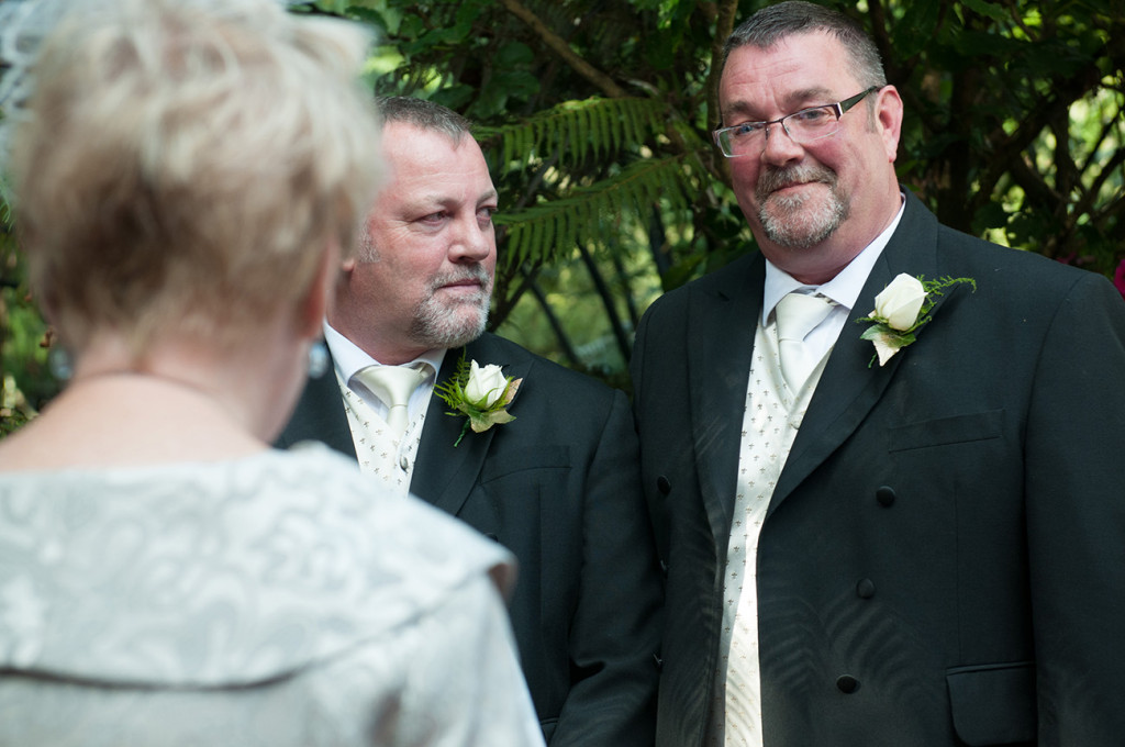 Groom looking at his husband as they listen to the celebrant Homosexual Home garden Wedding Auckland Photographer Anais Chaine