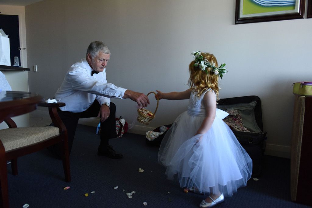 wedding photographer Takapuna flower girl holds her flower basket to her grand father before the wedding