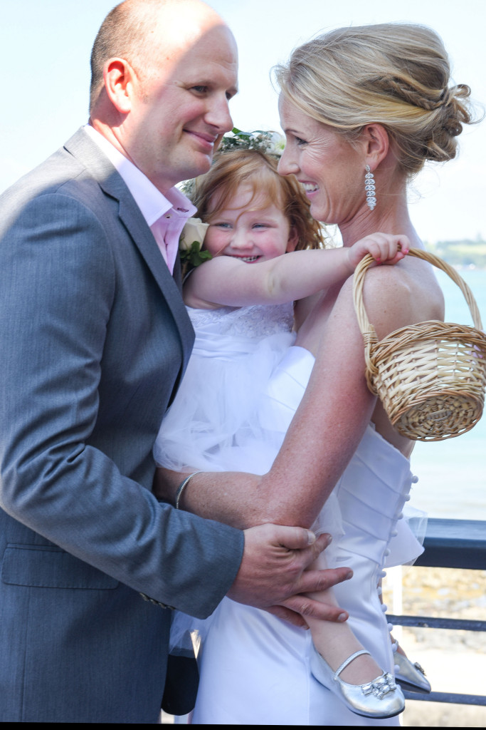 wedding photographer, Devonport, Duder's, the bride and groom hold her daughter between them after the yes I do