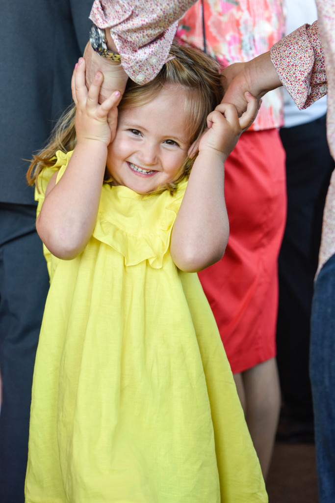 wedding photographer, Devonport, Duder's, a little girl with a yellow dress is smiling while holding hands on her head
