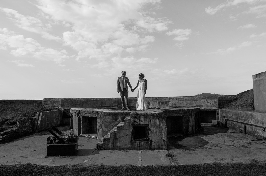Black and white in the middle of ruins lovers hand in hand looking each other