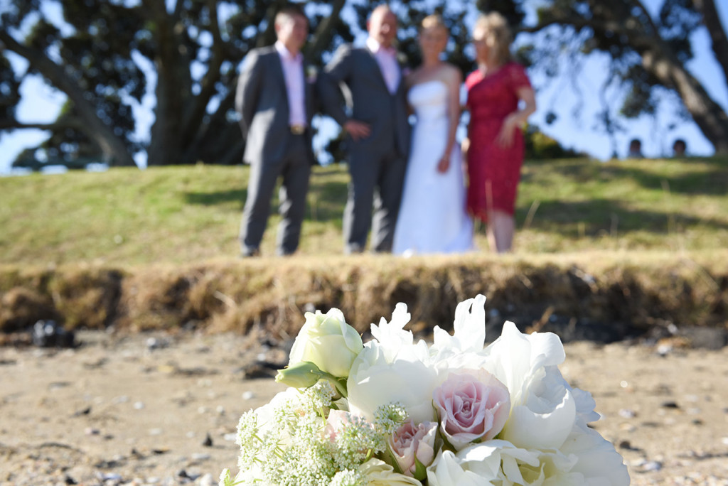 wedding photographer, Devonport, Duder's, composition with the bride's bouquet in front and the bride and groom and their bridel party in the back