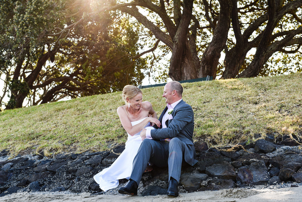 wedding photographer Devonport Duder's the bride and groom are seated on the rocks and played laughed together