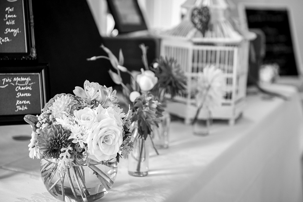 Table decoration with flowers picking by hand and blurred birdcage in the background