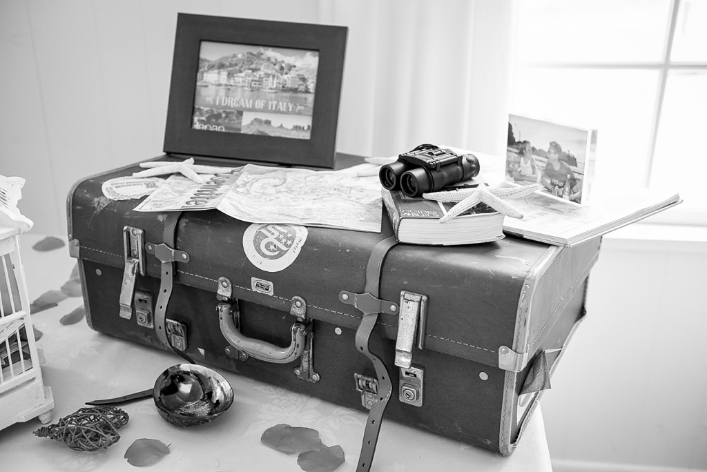 black and white old suitcase with different travel' stuff putting on a table