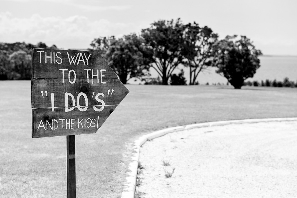 "Highway sign with this inscription ""This way to the 'I do's' and the kiss!"" pointing the way out"