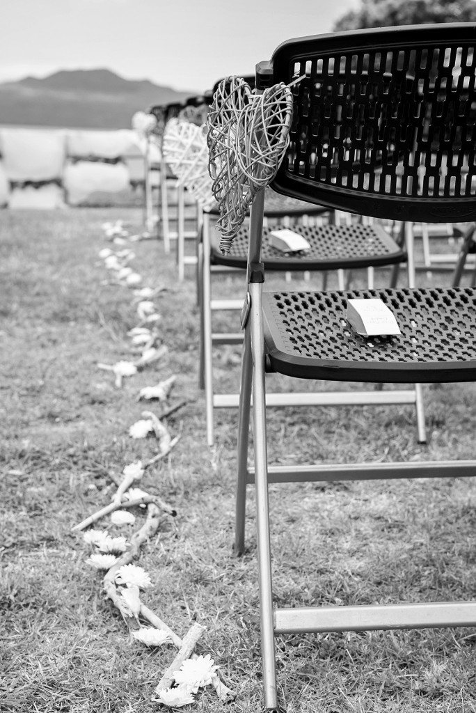 Black and White guests' chairs and decoration for the ceremony hearts flowers and pieces of wood