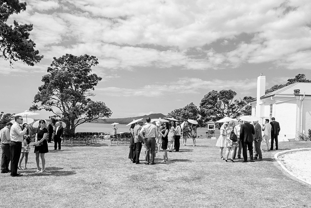 Black and white Guests waiting outside the beginning of the ceremony with sunshade