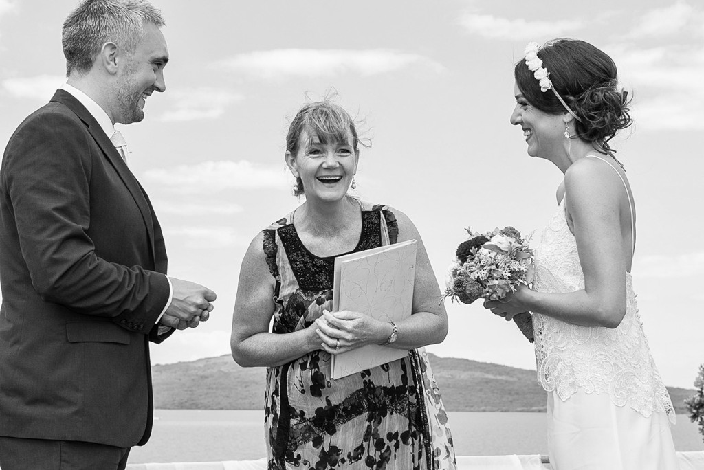 The bride and groom face to face and the celebrant laughing of hapiness