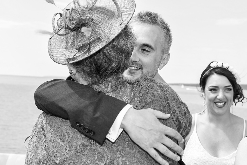 The groom's mother taking her son in her arm after the yes I do
