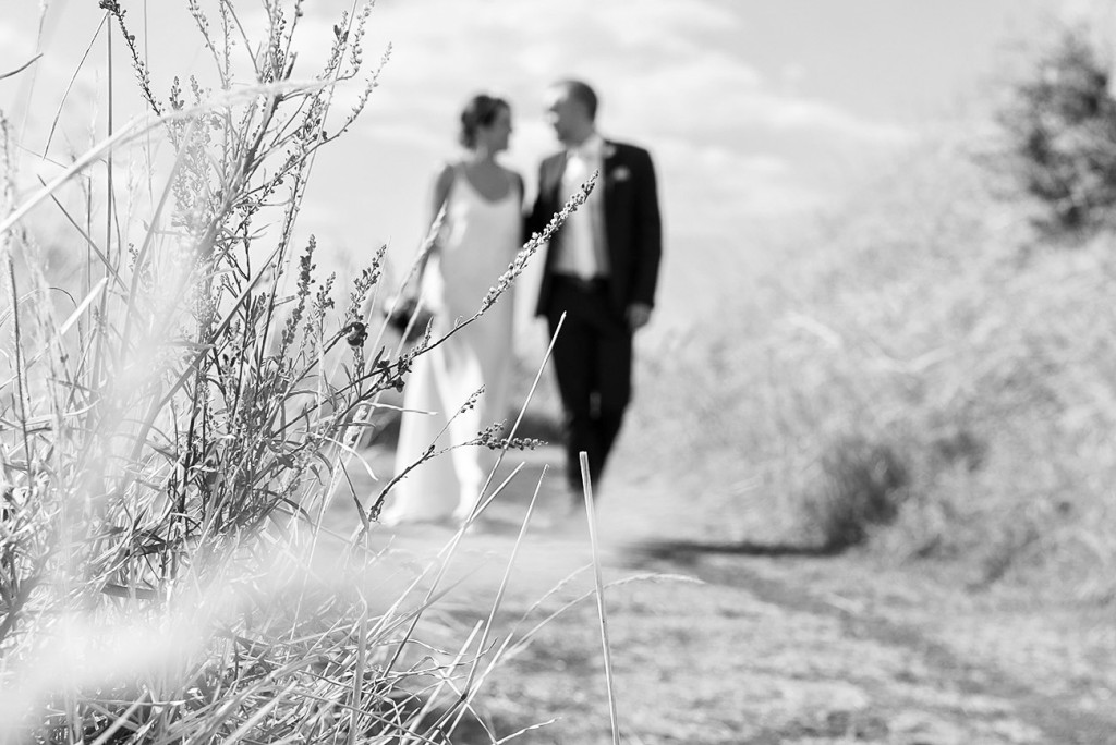 Focus on plants at the edge of the way the bride and groom blurred walking