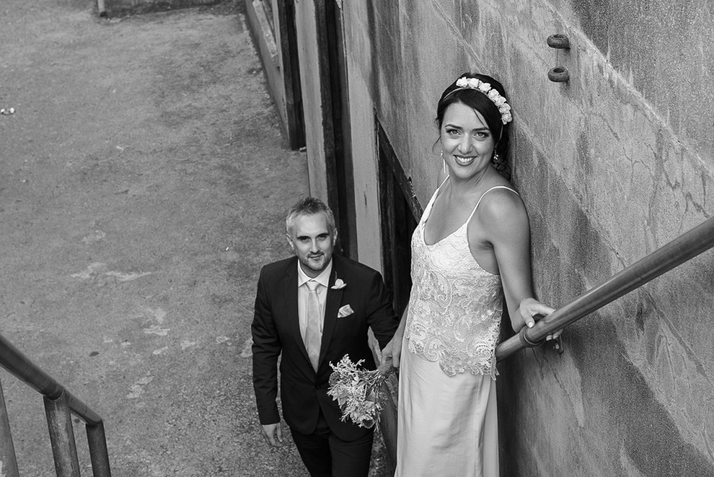 Mise en scene in stairs with the bride in the foreground back to the wall and the groom in the background