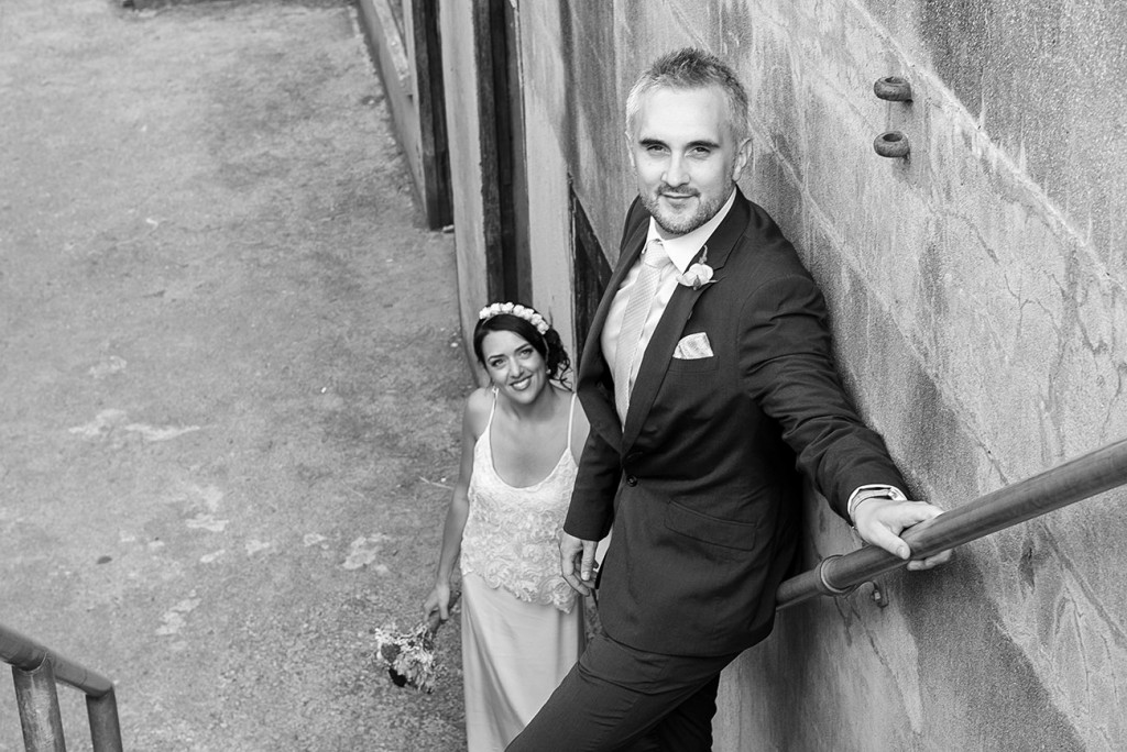 Mise en scene in stairs with the groom in the foreground back to the wall and the bride looking at him in the background