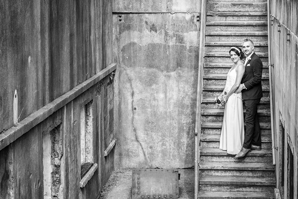 In a space closed down the bride and groom keeping together in the stairs