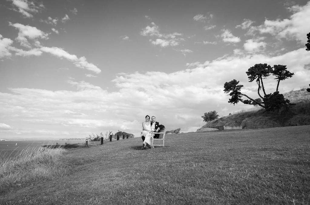 Seating on the bench the bride and groom are on the middle of a beautiful landscape black and white