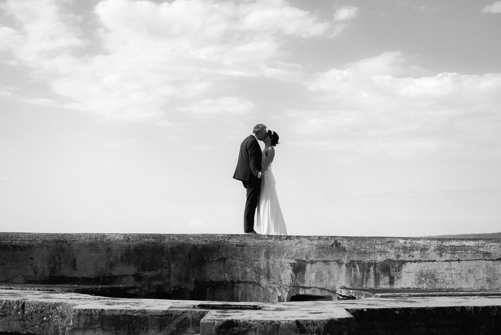 the bride and groom kissing in front of the sea black and white wedding photographer
