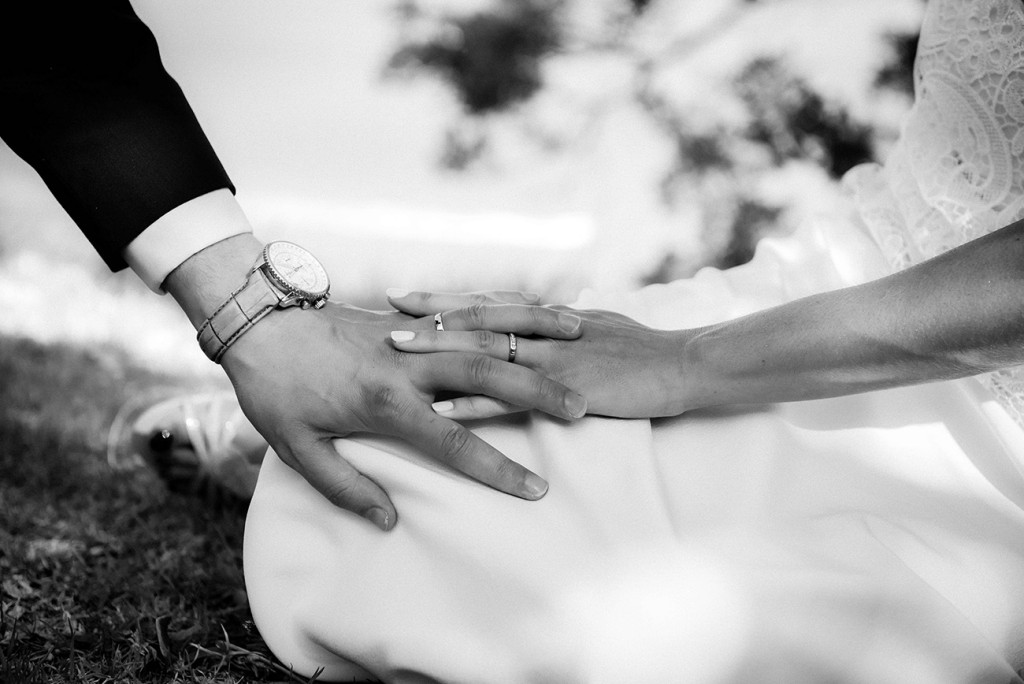 The bride and groom holding hands with their new rings