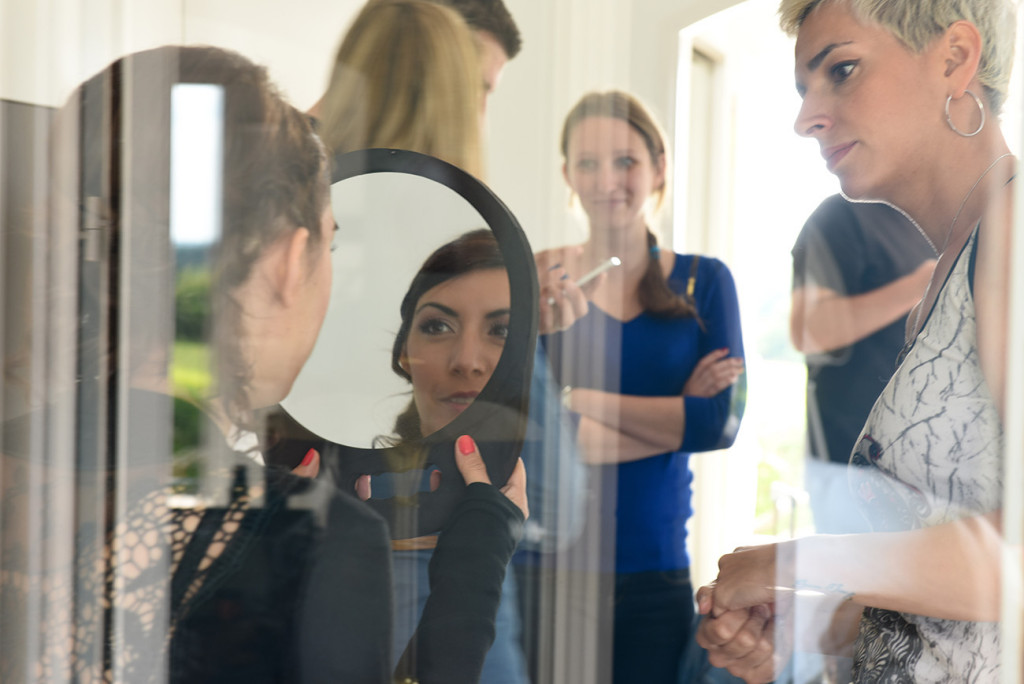 Reflection of one of bridesmaid checking her makeup in the mirror