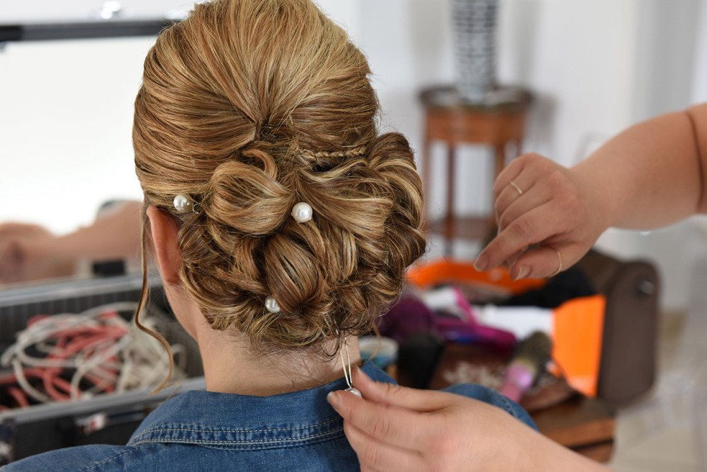 The back of the bride's wedding hairstyle during hairdresser finishing to set up barrette