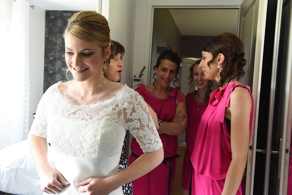 Behind the bride her mother and her bridesmaids chatting and laughing