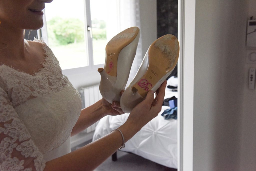 "Half-cropped of the bride showing proudly the bottom of her shoes where indicating ""I Do"""