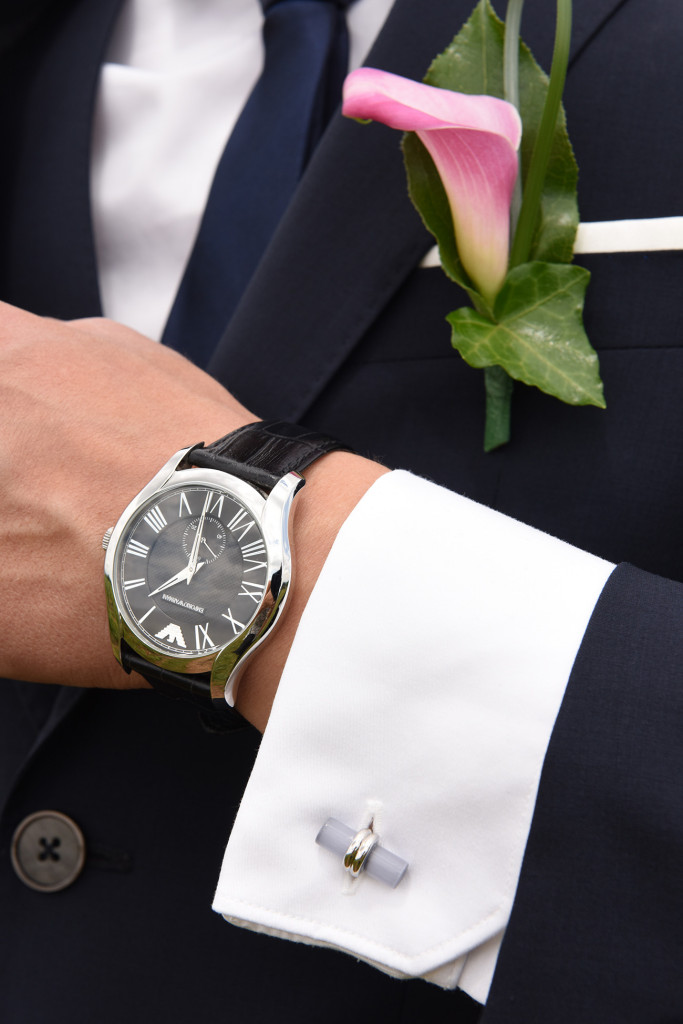 Zoom on the groom's accessories his watch a flower in his buttonhole and cufflink