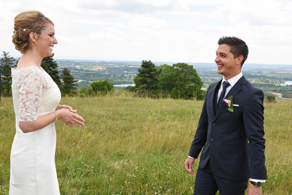In front of a beautiful french landscape the bride and groom smiling when they discovering each other