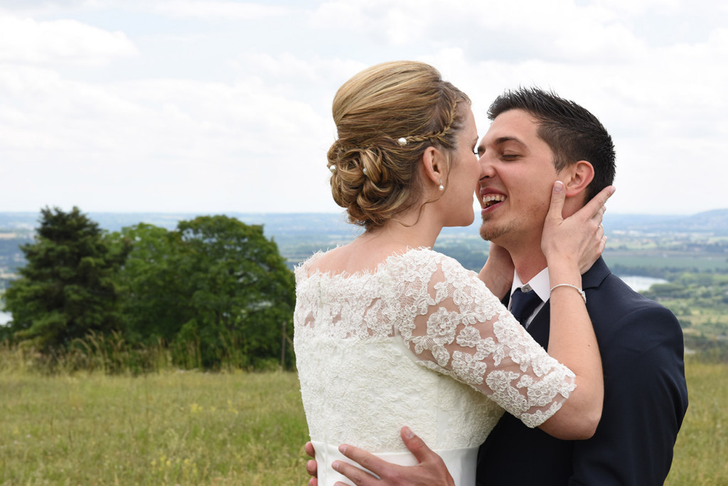 The bride and groom kissing in front of a beautiful french landscape