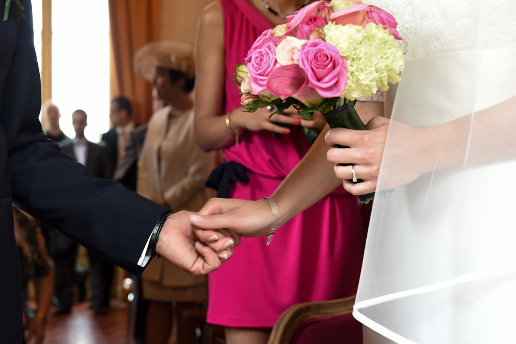 Half-cropped of the bride and groom's hands holding each other during the ceremony in the city hall
