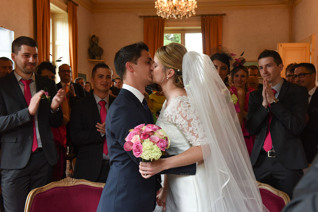 In the background the guests applauding the bride and groom kissing during the ceremony in the city hall