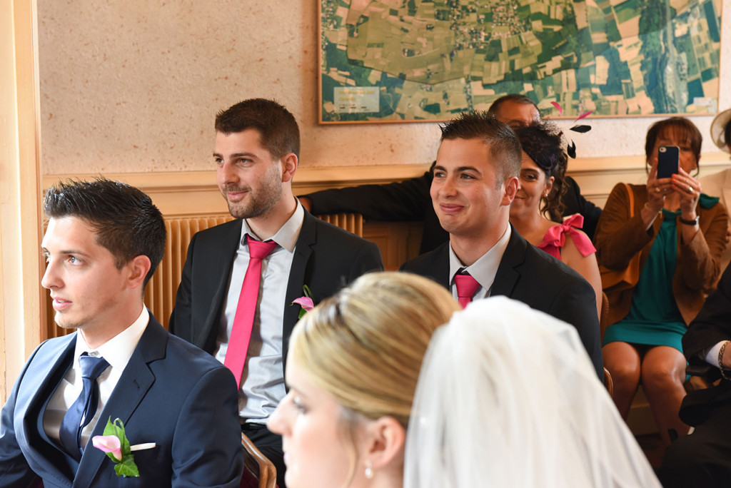 Groomsmen smiling during the ceremony in the city hall