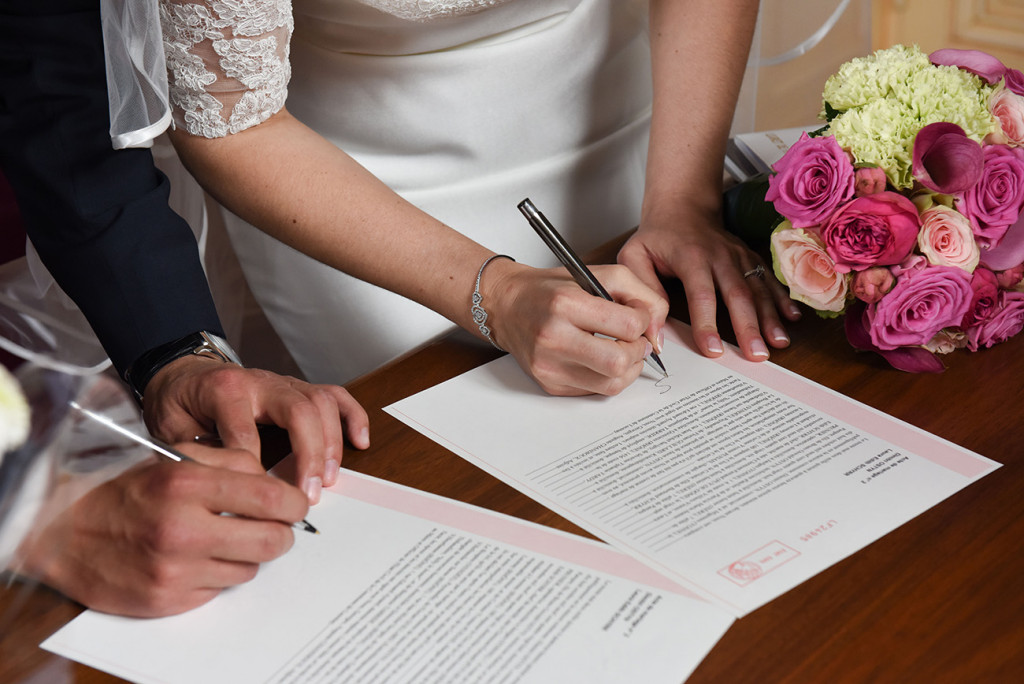 Half-cropped of the bride and groom signing official papers of their union