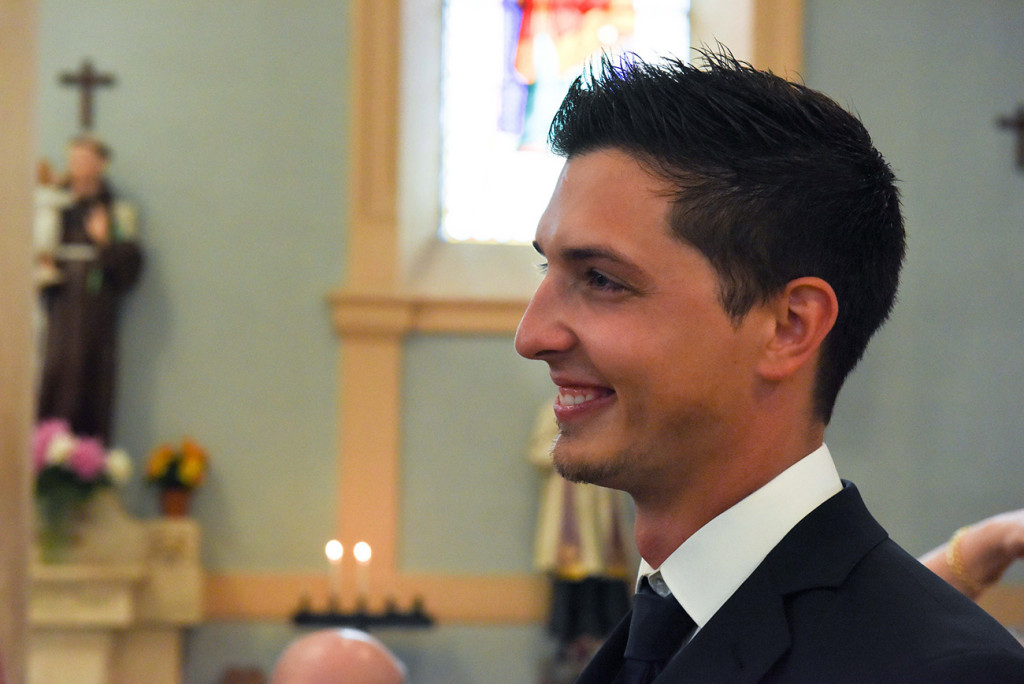 The groom smiling when he see the bride arriving at the altar