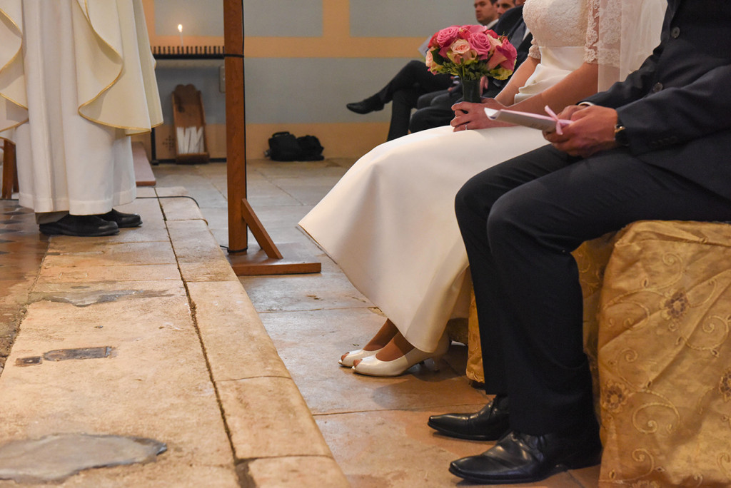 Half-cropped of the bride and groom and the priest's lower body during the ceremony in the church
