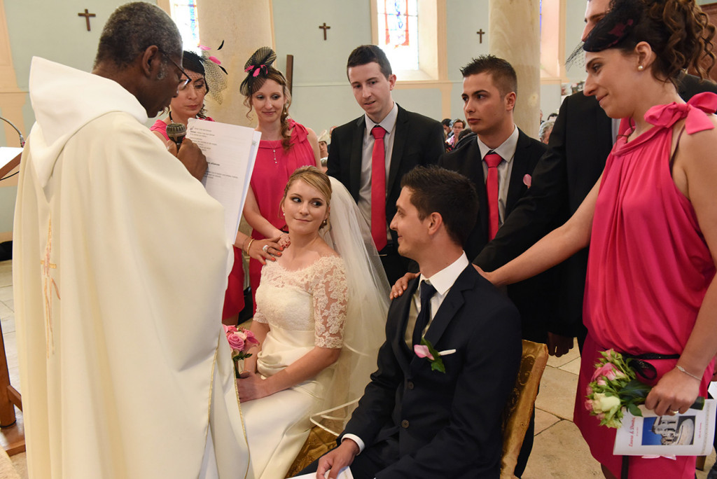 The bride and groom looking at each other and seating in front of the priest and surrounded by their bridesmaids and groomsmen during the ceremony in the church