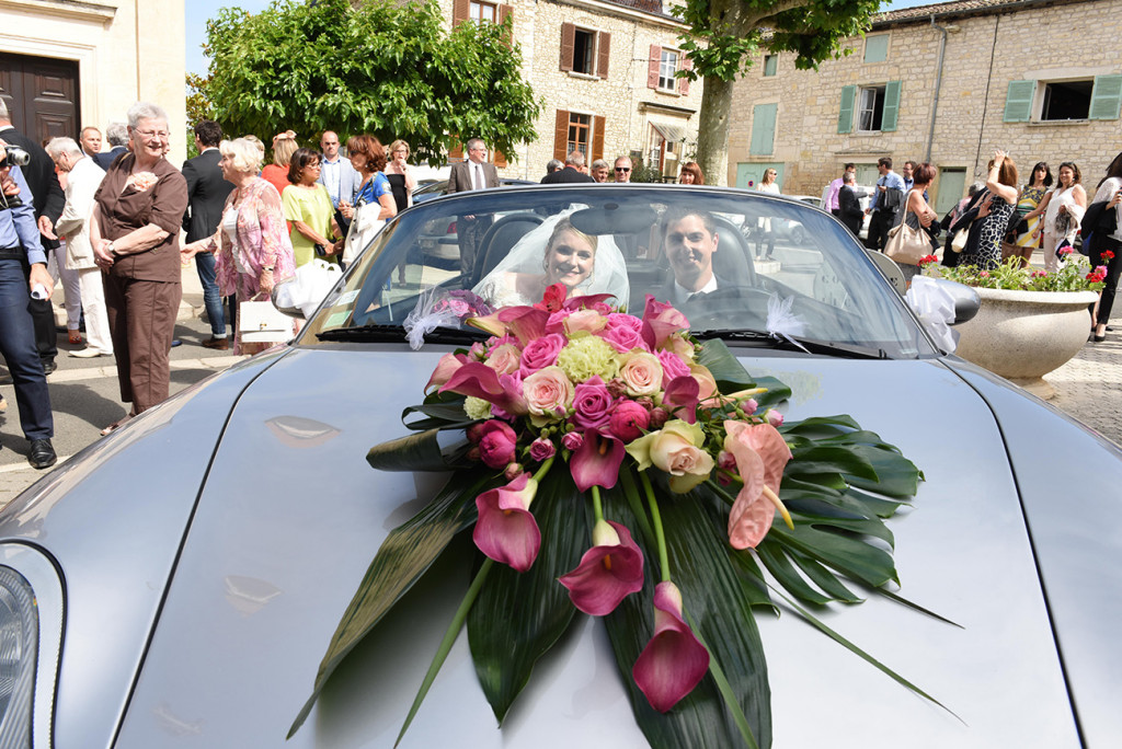 The bride and groom seating in the wedding car embellished with a magnificent bouquet on the hood