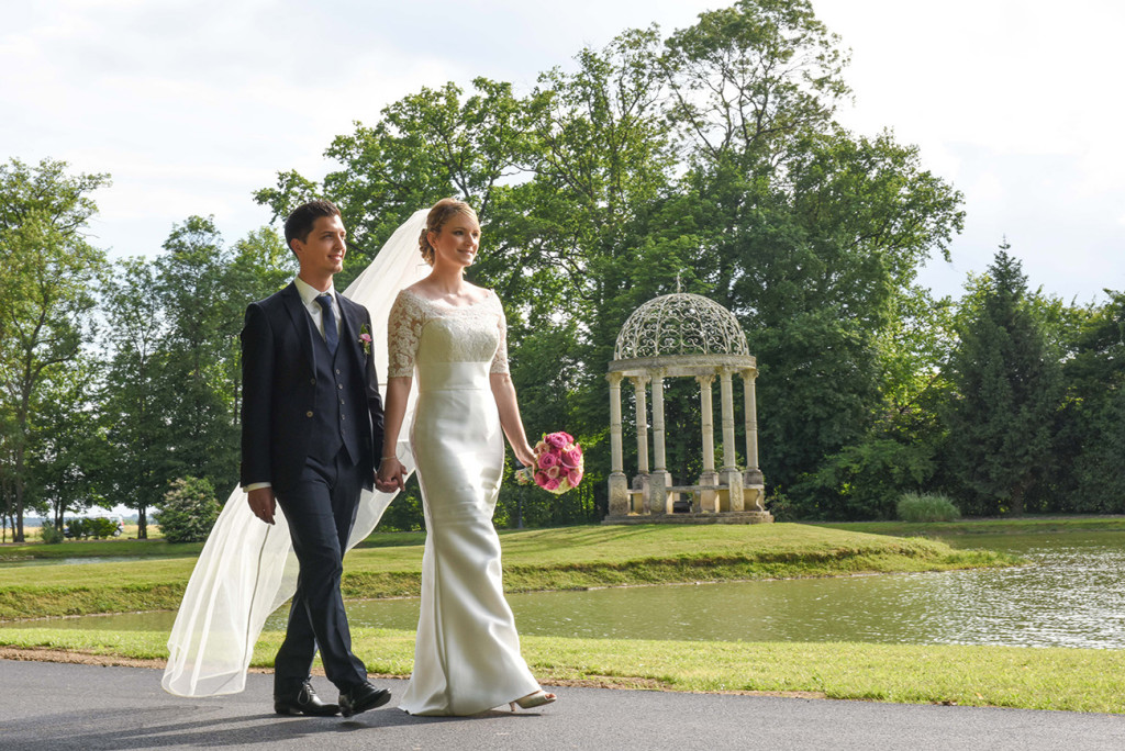 Hand in hand the bride and groom walking in the beautiful garden of Château d'Epeyssole