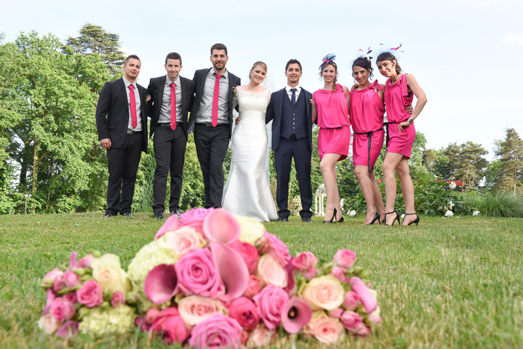 Alignment of the bride and groom surrounded by their bridesmaids and groomsmen in the background and blurred wedding bouquet in the foreground