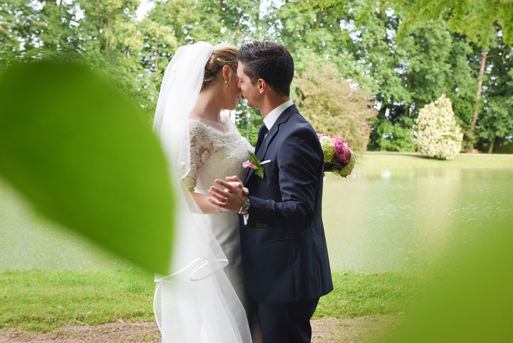 Behind blurred green leaves the bride and groom dancing in a beautiful garden