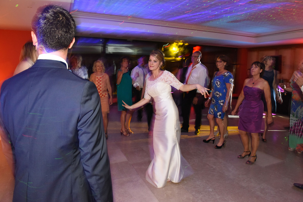 The bride dancing in front of the groom and surrounded her guests
