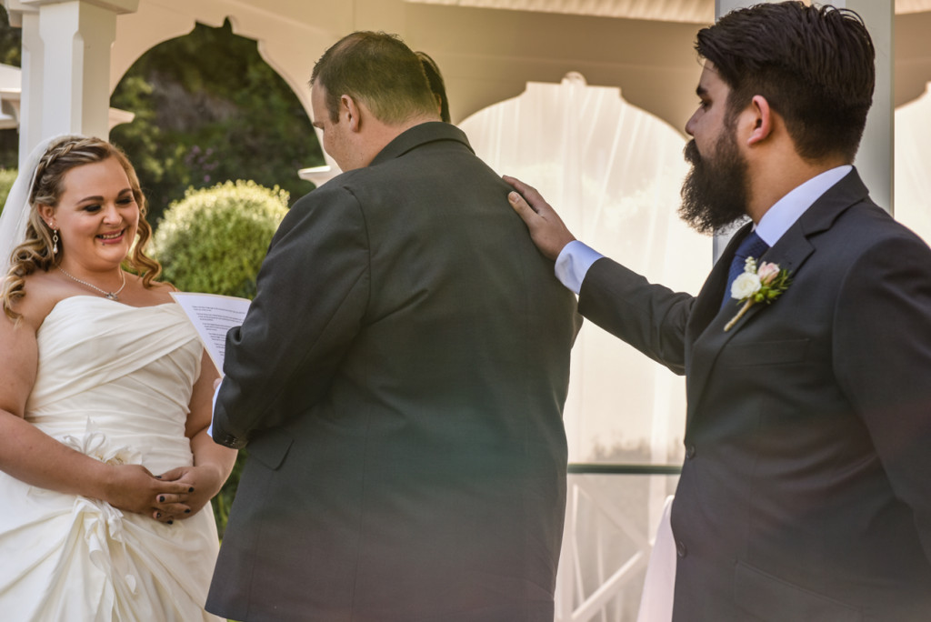 The bestman taps the groom on his back while he reads his vows