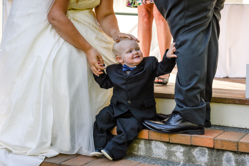 Mini groomsman at the aisle with his parents