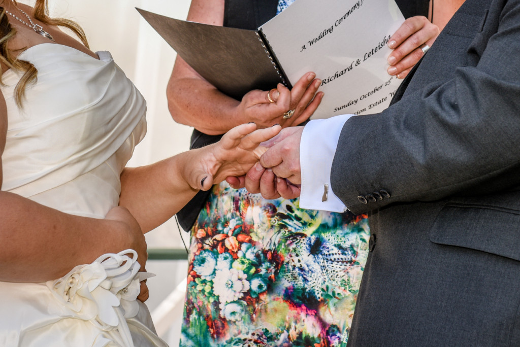 Groom slips the ring onto the bride's finger