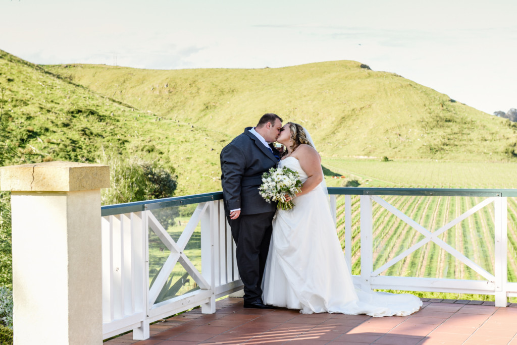 Bride and groom kiss with the winery as backdrop