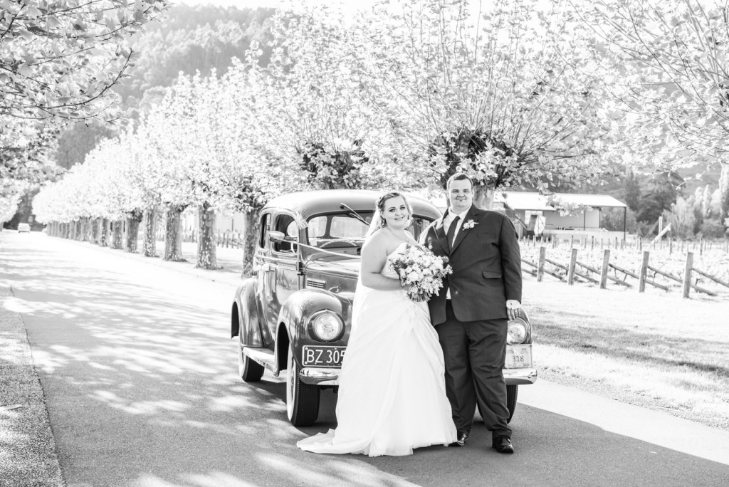 Bride and groom pause infront of vintage car under cherry blossoms