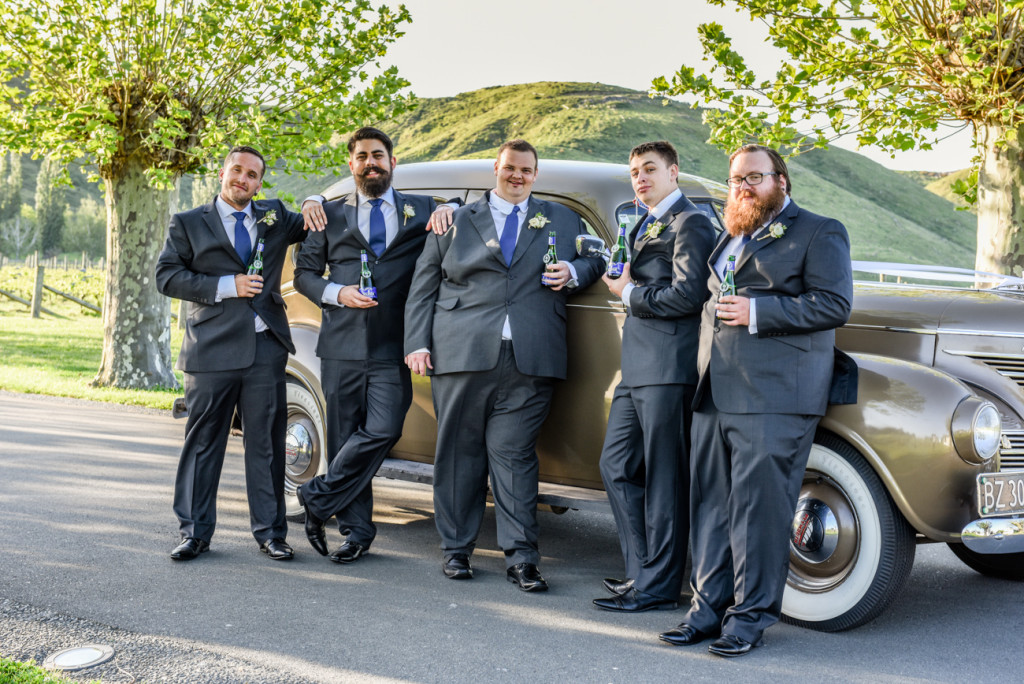 The groom and his groomsmen strike a pause infront of the vintage motorcade
