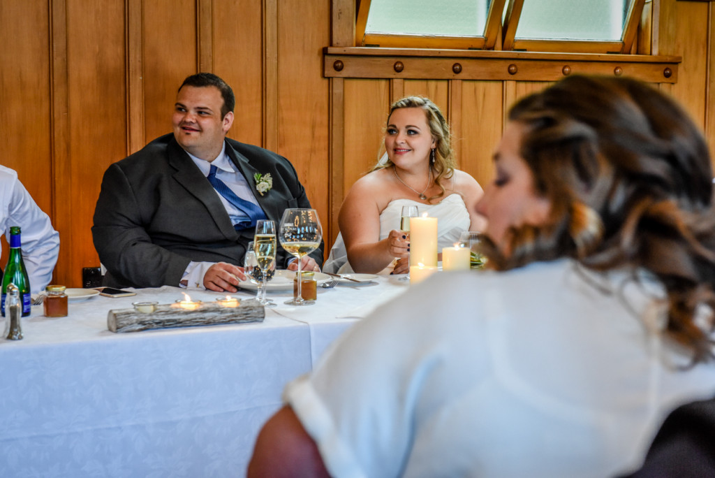 Bride and groom watch as friend raises toast