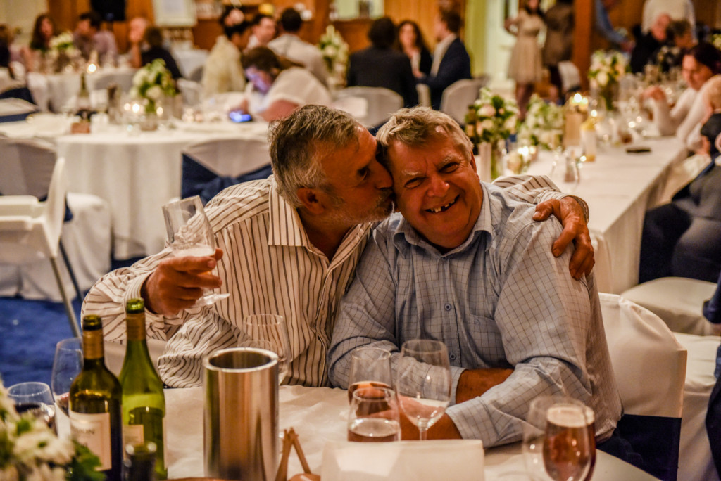 A gay couple kiss at the wedding reception