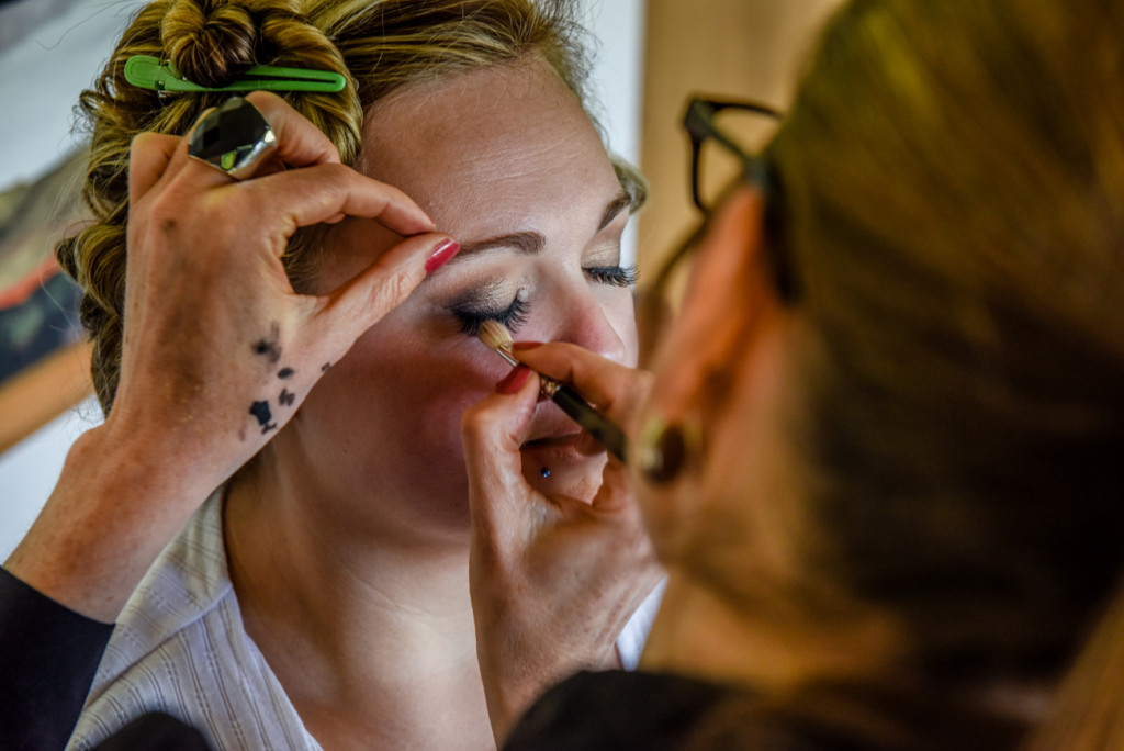The bride getting her makeup touched up by Jodie Brenstrum before her big day