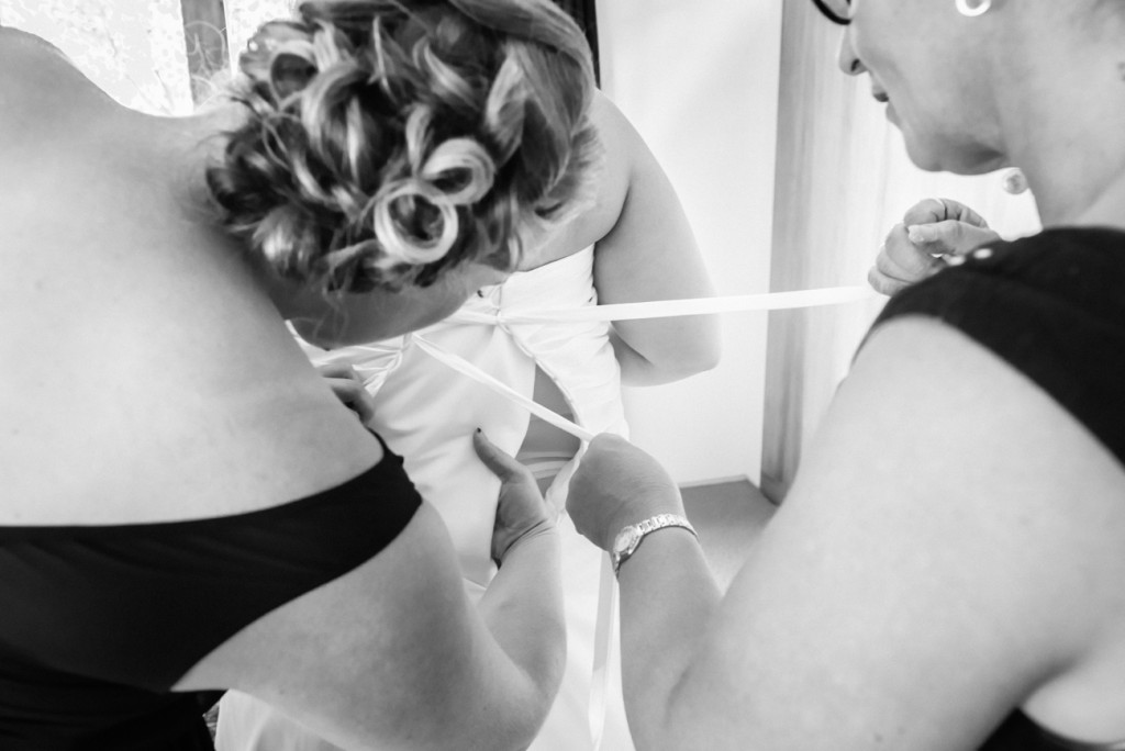 Bridesmaids fastening the bride's bodice